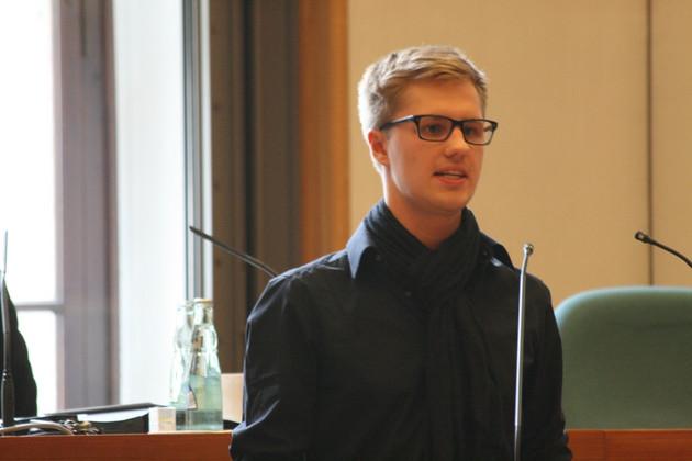 Georg Heyn (Vorsitzender des Stadtschuelerrats) steht vor einem Rednerpult und spricht.