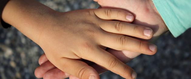 zur Hilfe ausgestreckte Hand, zweite Hand liegt obenauf