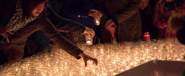 Eine Frau stellt ein Glas mit Teelicht zwischen viele andere Lichter, die bereits auf der Fläche stehen.