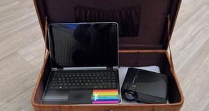 Ein Laptop und ein Beamer in einem geöffneten, alten Reisekoffer