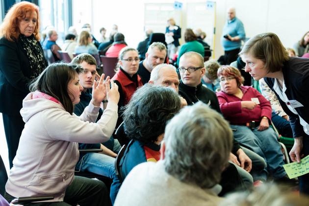 Eine Gruppe Menschen sitzt im Kreis. Eine junge Frau gestikuliert und erzählt etwas. Mehrere Frauen und Männer schauen ihr aufmerksam zu.
