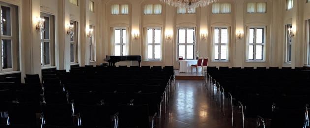 Saal mit großen Fenstern, Stuhlreihen und Kronleuchter