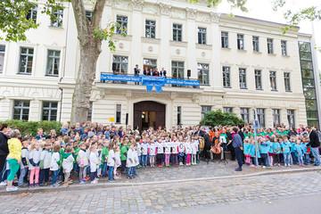 Bild wird vergrößert: Eine große Gruppe Grundschulkinder steht vor dem Schumann-Haus. Am Balkon hängt eine große blaue Scherpe mit Schleife.