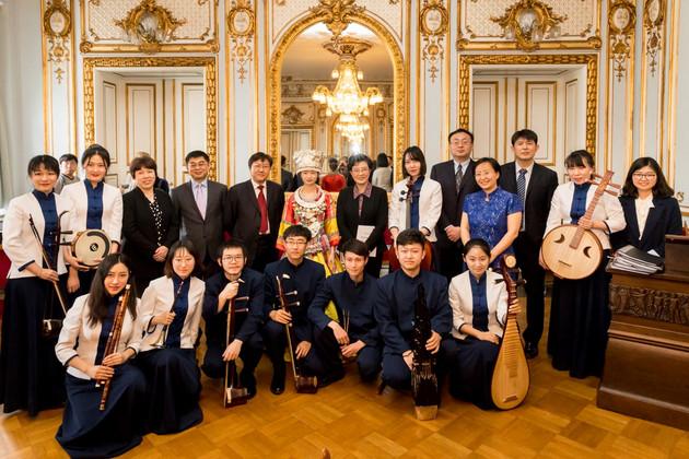 Eine Gruppe chinesischer Musikerinnen und Musiker posiert mit asiatischen Instrumenten in einem reich mit Gold und Stuck verzierten Saal.