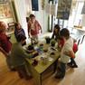 Eine Gruppe von Schülern steht im Apothekermuseum um einen Tisch und beobachtet die Vorführung der historischen Waage. Es werden Gewürze und Heilkräuter abgewogen.