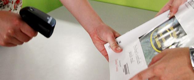 Eine Broschüre wird in den Händen gehalten und mit einem Scanner erfasst.