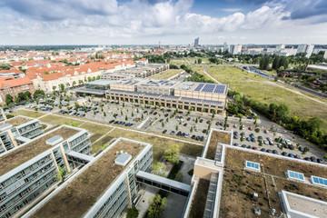 Bild wird vergrößert: Blick von oben auf das MDR-Gelände und MediaCity mit vielen Gebäuden, einem Parkplatz und weit dahinter der Leipziger Innenstadt