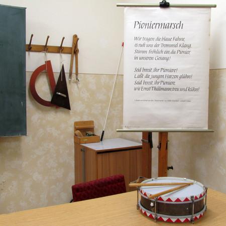 Blick in das Klassenzimmer zur DDR-Schule 1985 mit Tafelutensilien, Rollbild mit Pioniermarsch und Trommel.