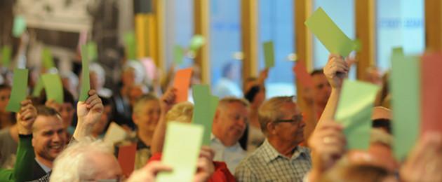 Bürgerinnen und Bürger halten rote und grüne Karten zur Abstimmung hoch.