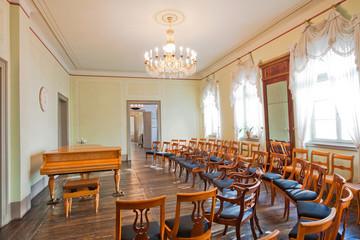 Bild wird vergrößert: Verzierter alter Musiksalon mit Kronleuchter und mit einem Flügel, davor mehrere Stuhlreihen
