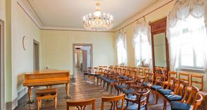 Verzierter alter Musiksalon mit Kronleuchter und mit einem Flügel, davor mehrere Stuhlreihen