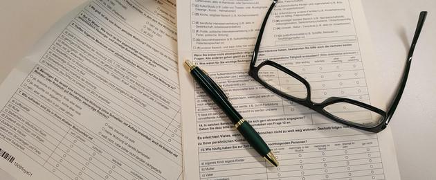 Fragebogen auf einem Tisch, darauf liegen ein Stift und eine Brille.