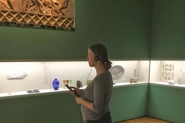 Bild wird vergrößert: Eine Frau steht in einem Ausstellungsraum mit Kopfhörern und wählt über eine Fernbedienung den passenden Beitrag aus.