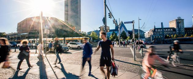 Blick auf den Augustusplatz. Viele Menschen überqueren gerade die Kreuzung.