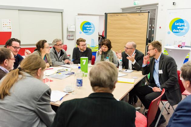 Eine Gruppe von Menschen sitzt an einem Tisch und diskutiert.