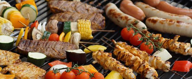 Gemüsespieße und Würstchen liegen auf einem Grillrost