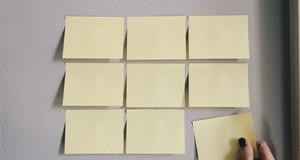 9 unbeschriebene Post-It-Zettel kleben an einer Wand. Eine Hand nimmt den unteren rechten Zettel weg.