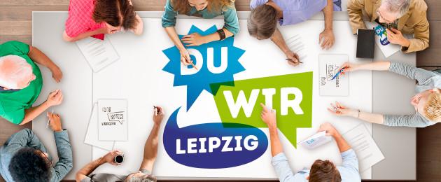 """An einem Tisch sitzen viele Menschen und reden miteinander. Einige halten Stiften und schreiben. Darauf das Logo """"Du Wir Leipzig"""""""