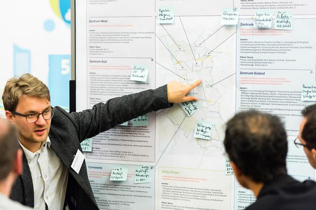 Diskussion an der Moderationswand. Ein Mann zeigt auf einer Tafel und schaut seine Zuhörer an.
