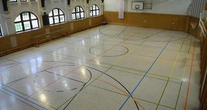 Sporthalle mit verschiedenen Bodenmarkierungen für unterschiedliche Sportarten und einem Basketballkorb an einer Wand.