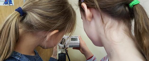 Zwei Mädchen - von hinten fotografiert - schauen auf ein Stromverbrauchsmessgerät, um den gemessenen Wert abzulesen.