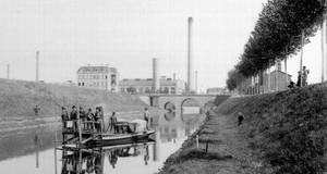 Historische Aufnahme vom Bau des Karl-Heine-Kanals mit Industriegebäuden im Hintergrund und Bauarbeitern auf einem Boot