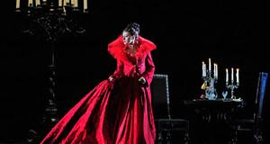 Szene aus Tosca in der Oper Leipzig: Frau in rotem langen Kleid auf dunkler Bühne