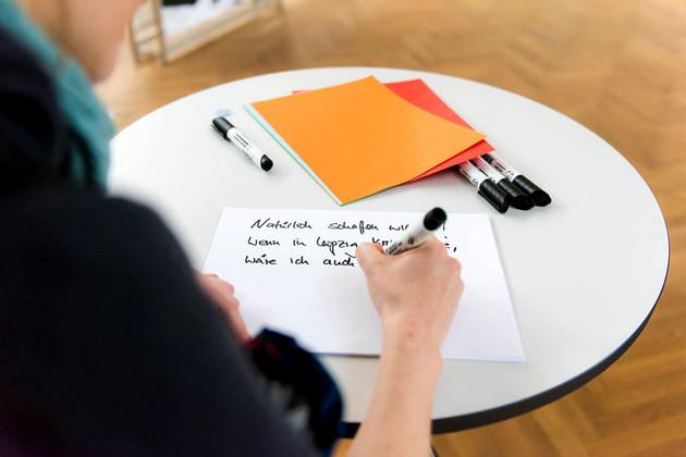 Eine Frau schreibt auf ein weißes Blatt auf einem Stehtisch.