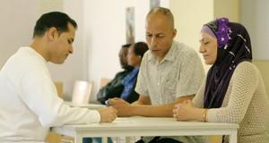 Arzt im Gespräch mit Asylsuchenden bei der Erstuntersuchung