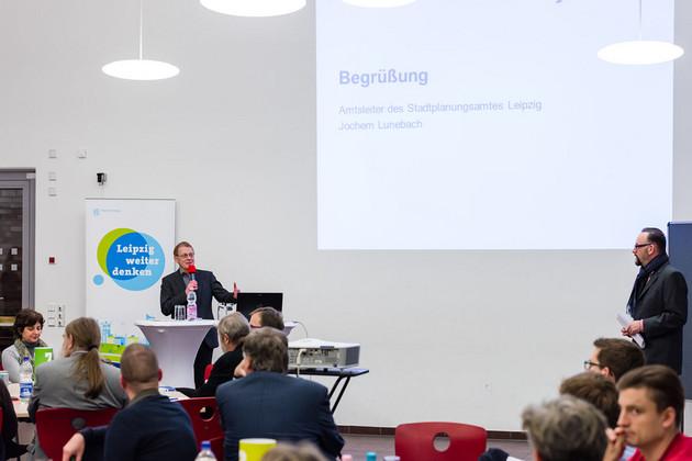 Ein Mann steht vor der Projektion einer Präsentation und hält eine Rede. Im Raum sitzen Menschen und hören zu.