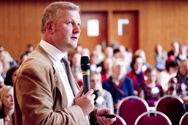 Ein Mann in hellem Anzug. Er blickt nach oben und hält dabei ein Mikrofon. Im Hintergrund ist verschwommen das Publikum zu erkennen.