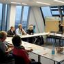 Zehn Menschen sitzen in einem Workshop vor einer Glasfront, die Moderatorin pinnt Karten an