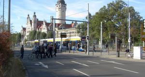 Straße und eine Straßenbahnhaltestelle mit dem Neuen Rathaus im Hintergrund