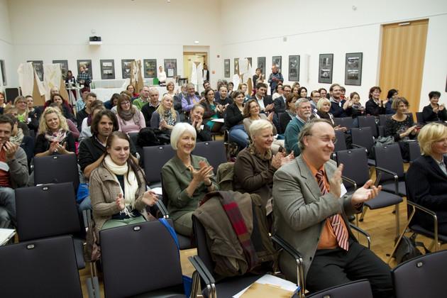 Zahlreiche applaudierende und lachende Menschen in Reihen sitzend.