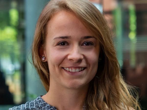 Eine junge Frau mit langen braunen Haaren lächelt ins Bild.