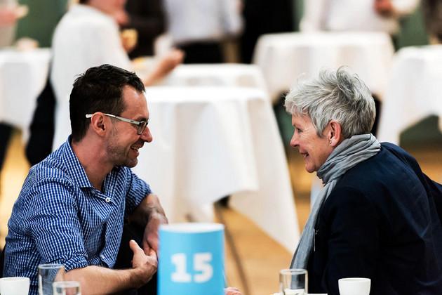 Ein Mann und eine Frau unterhalten sich und lächeln dabei. Im Hintergrund Stehtische.