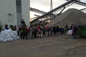 Bild wird vergrößert: Helfer stehen in einer Schlange und befüllen Sandsäcke, um dem Hochwasser 2013 entgegenzuwirken