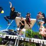 Vier männliche Jugendliche springen von der Bühne richtung Kamera (aus der Froschperspektive fotografiert).