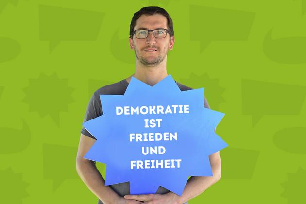 """Ein Mann hält ein Schild mit dem Statement """"Demokratie ist Frieden und Freiheit.""""."""