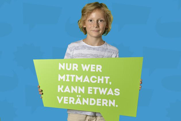 """Ein Junge hat sich mit dem Statement """"Nur wer mitmacht, kann etwas verändern."""" auf einer grünen Sprechblase fotografieren lassen."""