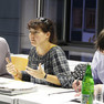 Drei Menschen sitzen an einem Tisch, eine Frau in der Mitte spricht