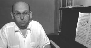 Hanns Eisler mit einem Notenblatt und einen Klavier beim Komponieren.