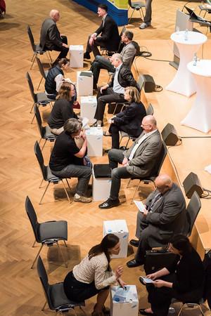 Blick von oben auf eine Stuhlaanordnung von 12 Stühlen, die sich gegenüberstehen.