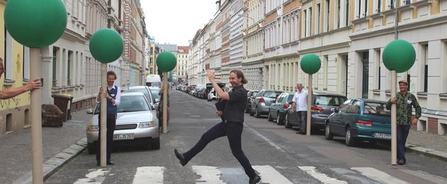 Ein Straßenabschnitt ist mit symbolischen Bäumen markiert. Jemand geht zwischen den Bäumen über die Straße.