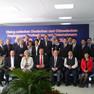 """Gruppenfoto einer großen Menschengruppe vor einem lila Werbeplakat, auf dem der rote Schriftzug """"Dialog zwischen deutschen und chinesischen Regierung, Professoren und Unternehmen"""" steht"""