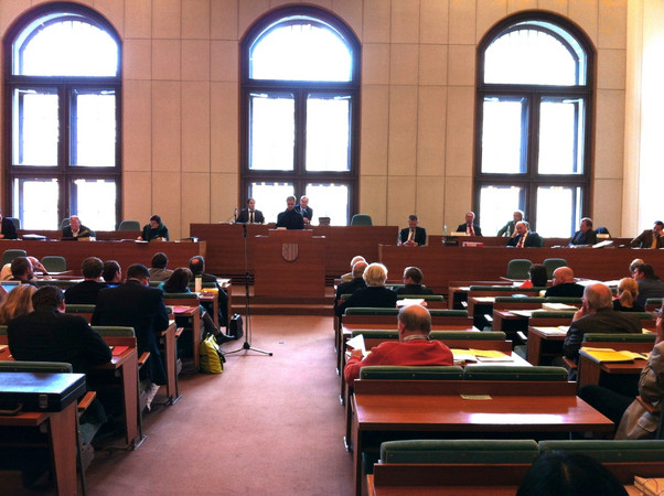 Blick von der letzten Reihe aus dem Zuhörerraum des Plenarssals in Richtung Rednerpult.
