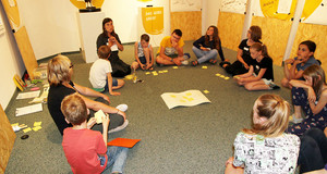 Jugendliche sitzen im Kreis, vor ihnen liegen gelbe Notizzettel.