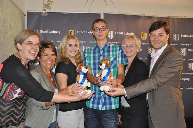 Fünf Personen halten zwei Kuscheltier-Löwen mit blauen Schärpen mit chinesischen Schriftzeichen lachend in die Kamera