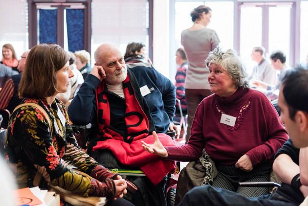 Drei Personen, ein Mann und zwei Frauen, sitzen zusammen. Eine der Frauen redet, die anderen hören aufmerksam zu.