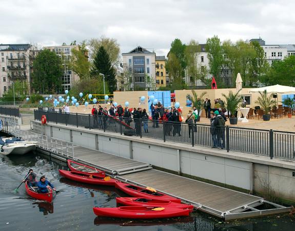 Fünf rote Kajaks, teils mit Menschen besetzt, befinden sich im Wasser. Etwa einen Meter erhöht befindet sich der Uferbereich mit Geländer und Schaulustigen.